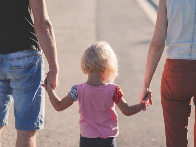 Young girl between her parents, holding their hand