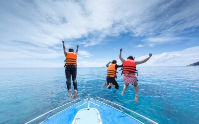 Three swimmers with life jackets hopping off of a boat